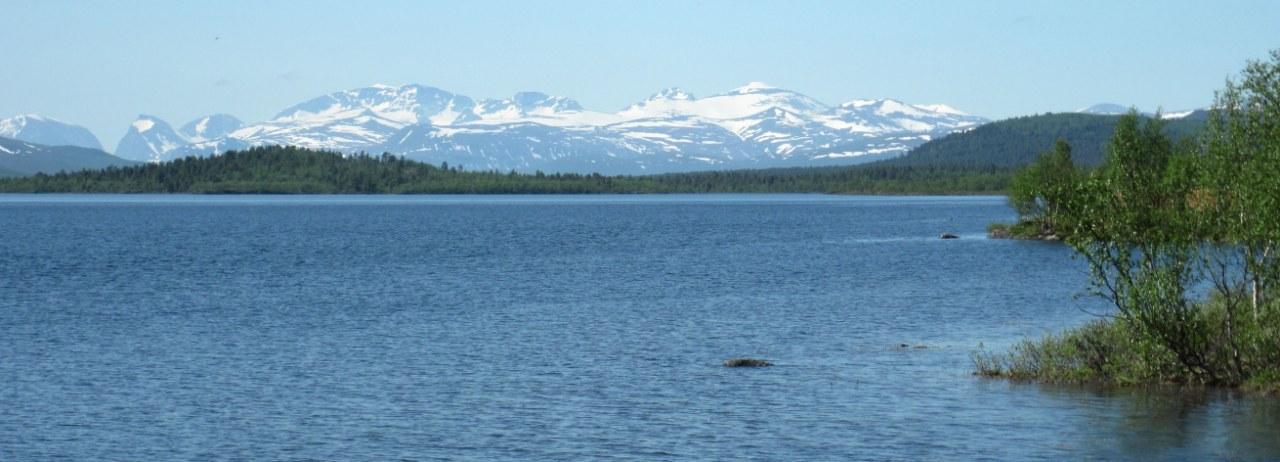 Een prachtig meer in het noordwesten van Zweden met op de achtergrond besneeuwde bergen van Noorwegen.