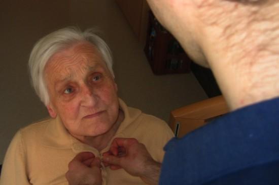Oude vrouw die geholpen wordt bij het aankleden. Is ze nog een beetje gelukkig of wil ze euthanasie?