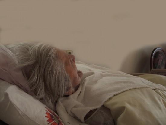 Oude vrouw in bed. Uitzichtloos en ondraaglijk lijden vormen redenen voor euthanasie.