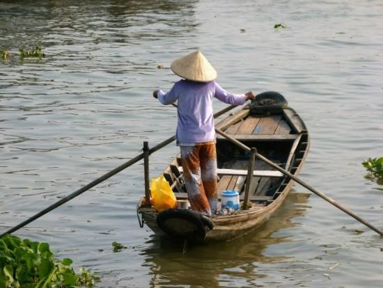 Aziatische vrouw met koopwaar op weg naar de markt. Buiten de westerse wereld blijven de grote inkomensverschillen tussen mannen en vrouwen nog decennialang in stand, vreest de ILO.