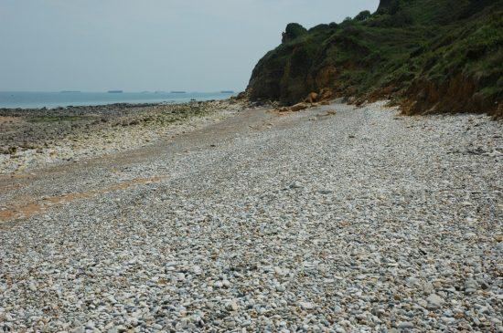 Renske Cramer Creatief foto van een kiezelstrandje aan de Normandische kust. Op de achtergrond ziet u in zee nog resten van betonnen pontons, die de geallieerden hebben gebruikt tijdens D-Day. e kust in de Basse-Normandie (Frankrijk)